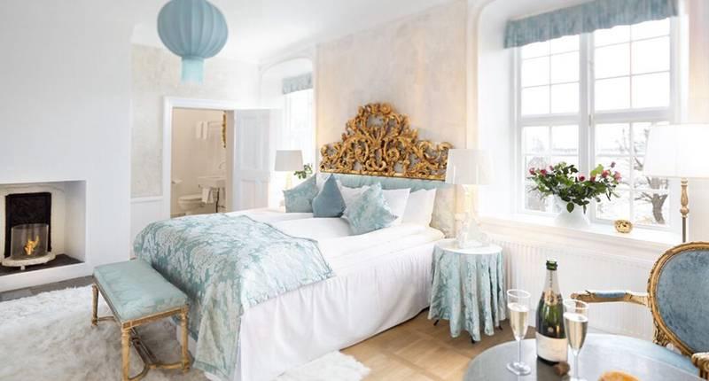 Ett romantiskt rum på ett slott. En mysig säng och en flaska champagne på ett bord bredvid sängen.