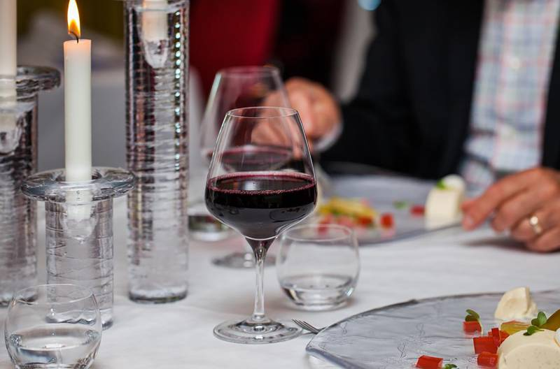 Ett dukat bord med tända ljus och två glas rött vin. en man i kostym äter en romantisk middag.