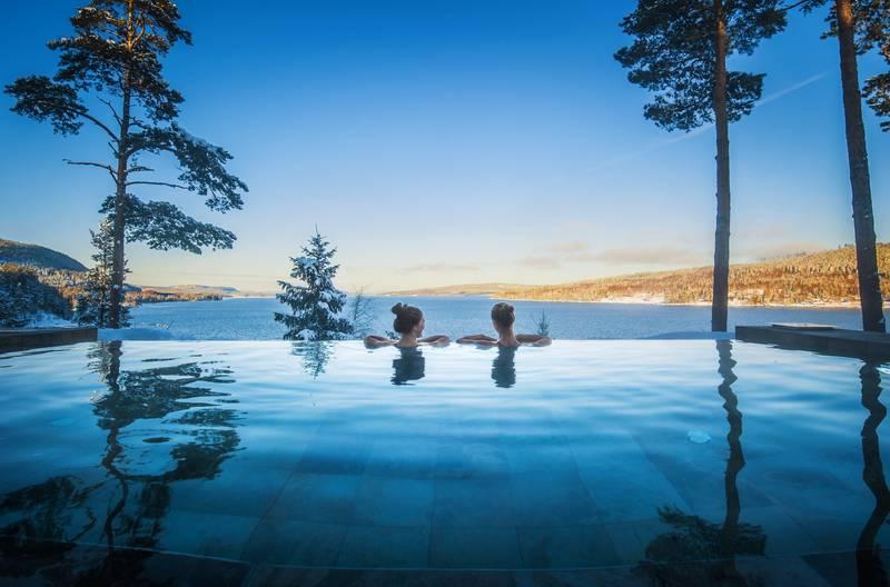 En utomhus pool, där ett kärlekspar beundrar den vackra utsikten. En sjö, skog och berg.