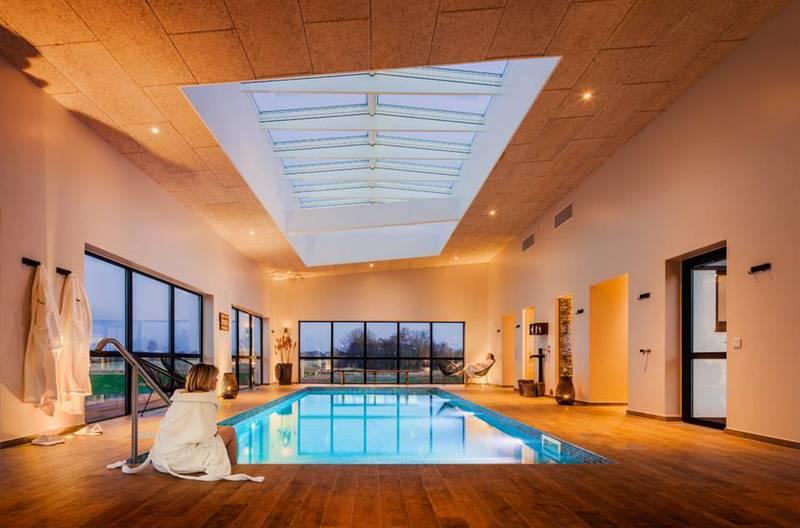 En pool inomhus i vackert ljus. En kvinna sitter vid poolkanten med morgonrock.