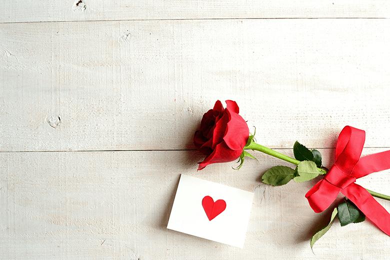En röd ros och ett kärleksfullt brev med hjärta på, som ligger på ett trä bord.