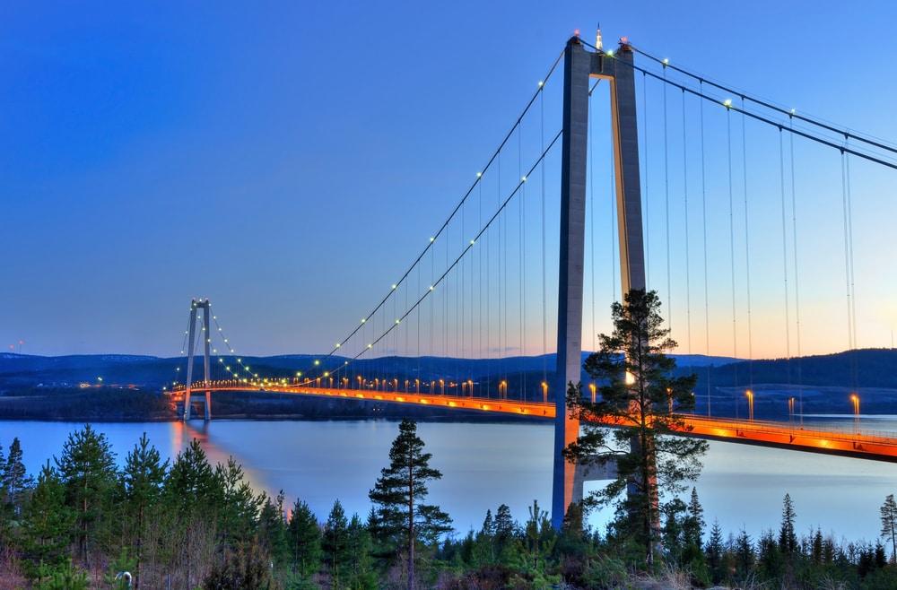 Högakustenbron över Ångermanälven på kvällen med lampor som lyser på bron.