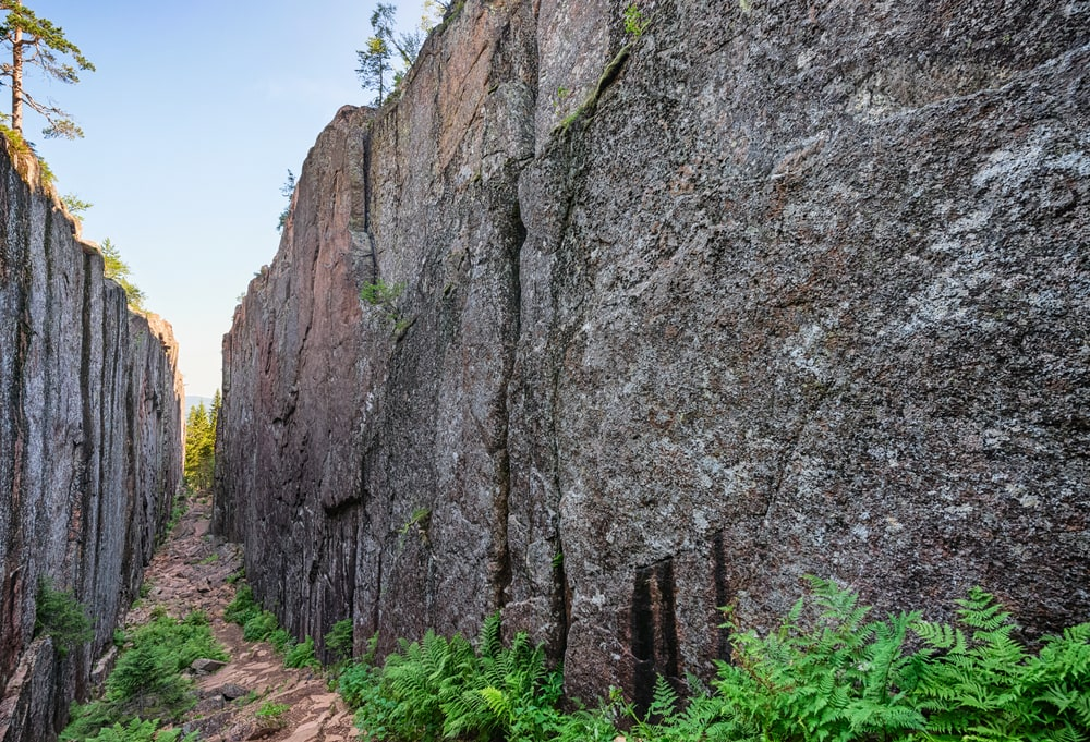 Slåttdalsskrevan i skuleskogens nationalpark. Här reser sig lodräta berg på varsin sida om stigen.