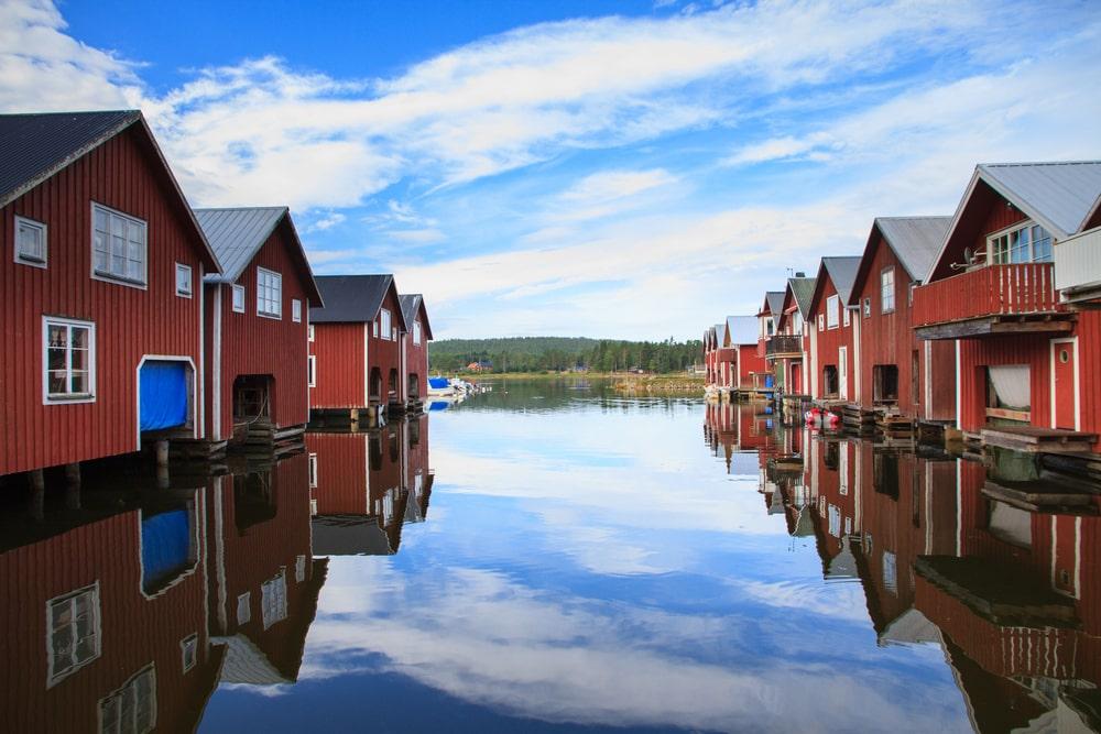 Röda fiskebodar som ligger precis vid havet på Ulvön i Höga Kusten
