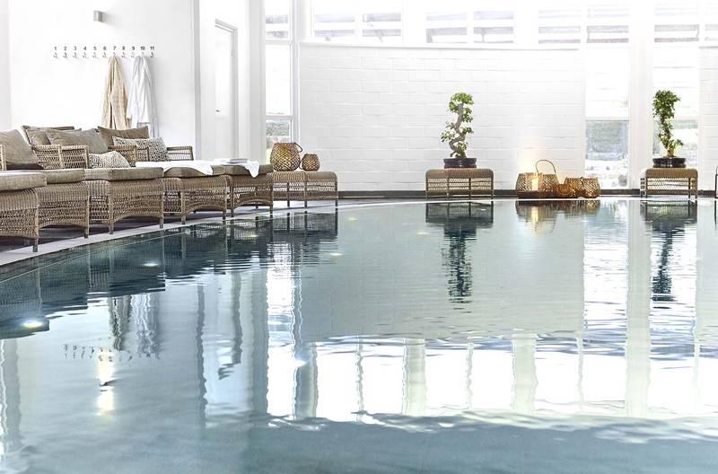 En inomhus pool på ett spa. Sköna fåtöljer vid poolkanten.