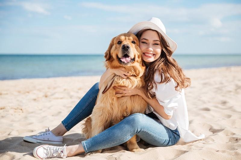 tjej som kramar en hund på en strand