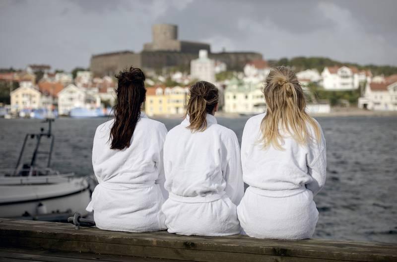 tjejer i badrockar tittar ut över marstrand